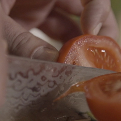 Chef is cutting a tomato